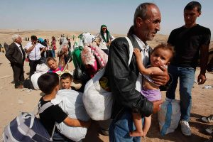 Syrian refugees, fleeing the violence in their country, cross the border into the autonomous Kurdish region of northern Iraq September 4, 2013. The Syrian refugee crisis may worsen if there is no international reaction in response to last month's alleged chemical weapons attack, Turkey's Foreign Minister Ahmet Davutoglu said on Wednesday. The two-year Syrian conflict has escalated, driving 2 million refugees abroad, uprooting 5 million within the country and taking at least 100,000 lives, Davutoglu said. Every day, about 5,000 Syrians cross the borders into Lebanon, Turkey and Iraq.  Picture taken September 4, 2013.  REUTERS/ Haider Ala (IRAQ - Tags: POLITICS CIVIL UNREST CONFLICT SOCIETY IMMIGRATION)